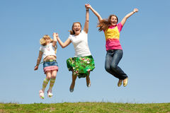 Happy Mom and two daughter jumping on green meadow Stock Image