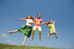 Happy Mom and two daughter jumping on meadow Stock Images