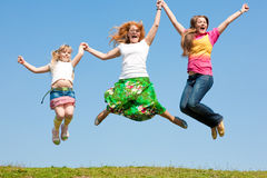 Happy Mom and two daughter jumping on meadow Royalty Free Stock Images