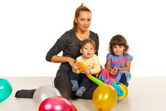 Happy mom with two kids. Happy mom with her kids sitting on floor with ballons Royalty Free Stock Images