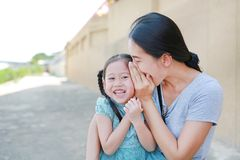 Happy mom whispering a something secret to her little daughter ear. Mother and kid communication concept stock images