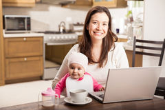 Happy mom working from home. Pretty young Latin single mother working from home on a laptop computer while spending time with her baby daughter stock photos