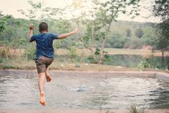 Happy moment Asian boy playing water in outdoor. Relax time and summer season Royalty Free Stock Photos