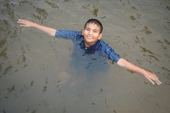 Happy moment Asian boy playing water in outdoor. Relax time and summer season Royalty Free Stock Photo