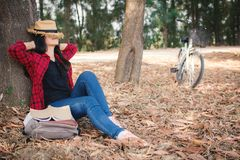 Happy moment hipster woman relaxing and sitting under the big tree on park. Enjoying time on holiday concept ,color of vintage tone and soft focus royalty free stock images