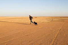 Happy moment: Man runs and plays with his dog in the desert. Stock Photo