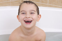 Happy Moments. Happy kid is smiling in the bathtub while his hair wet Stock Image