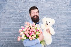 Happy moments. Love date. happy international holiday. happy bearded man with tulip bouquet and bear. Flower for March 8 stock photo