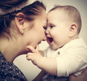 Happy moments. Mother holding and playing with her baby. Vintage Royalty Free Stock Image