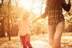 Happy moments together. Single mother and her little girl holding hands and running trough park together. Close up stock images