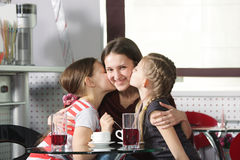 Happy mommy. Happy smiling mommy kissed by two daughters in cafe Royalty Free Stock Image