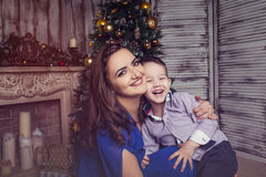 Happy mommy with laughing son in new year interior. Happy mommy holding little son in christmas interior stock image