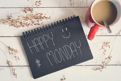 Happy Monday massage on notebook with coffee. Happy Monday massage on notebook with cup of coffee and flower on wooden table royalty free stock photo