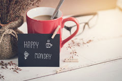 Happy Monday massage on notebook with coffee. Happy Monday massage on notebook with cup of coffee and flower on wooden table royalty free stock photos