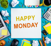 Happy Monday. Office table desk with supplies, white blank note pad, cup, pen, pc, crumpled paper, flower on blue Stock Image