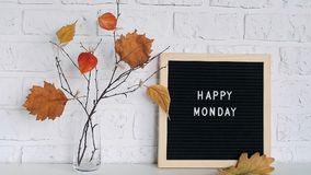 Happy Monday text on black letter board and bouquet of branches with yellow leaves on clothespins in vase on table. Template for postcard, greeting card Concept stock video footage
