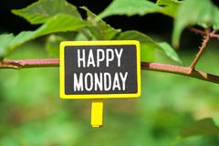 Happy Monday text on board. Happy Monday text written on yellow small chalkboard linked tree with clothespin on nature green background stock photography