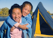 Happy Mongolian Girls Playing Piggyback Campsite Concept Stock Photos