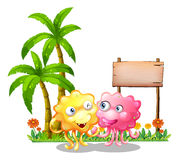 Happy monsters near the empty signage beside the palm trees Stock Image