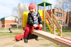 Happy 18 months baby on seesaw outdoors Royalty Free Stock Images