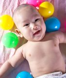 A happy 3 months old baby in a bath of balls stock photo