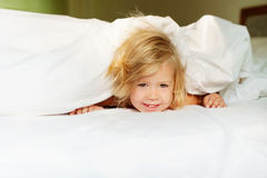 Happy morning baby. Happy baby in the morning peeps out from under the blanket stock photography