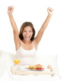 Happy morning breakfast woman. Smiling eating breakfast in bed stretching looking at camera. Beautiful morning fresh multicultural Asian Caucasian female model Royalty Free Stock Photos