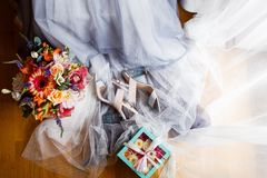 Happy morning of the bride. A bridal bouquet, a wedding dress, crystal shoes, the bride`s shoes, flowers in a box, blue Stock Photography