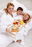 Happy morning and healthy food. Mother bringing breakfast to bed for her kids Stock Photography