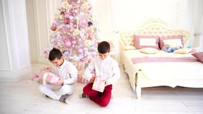 Happy morning after new year and opening of holiday gifts by children of boys in cozy bedroom with Christmas tree. Twin siblings with interest shake gifts and stock video