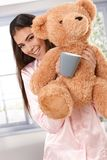 Happy morning portrait with teddy bear. Happy morning portrait of smiling attractive woman wearing pyjama with teddy bear and coffee mug Royalty Free Stock Photography
