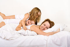 Happy morning - woman and kids on the bed Stock Images
