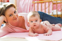 Happy mother. With her small baby lying on the bed Royalty Free Stock Photography