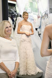 Happy mother admiring daughter dressed in a wedding gown royalty free stock photography