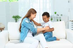 Happy mother with adopted African-American boy. Sitting on couch at home Stock Photography
