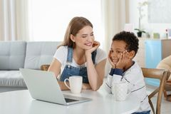 Happy mother with adopted African-American boy. Sitting at table in living room Royalty Free Stock Photos