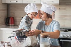 Happy mother and adorable child in chef hats preparing dough on messy table. At kitchen stock images