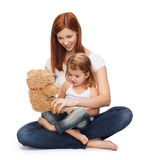 Happy mother with adorable girl and teddy bear. Childhood, parenting and relationship concept - happy mother with adorable little girl and teddy bear Royalty Free Stock Photo