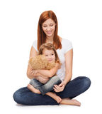 Happy mother with adorable girl and teddy bear. Childhood, parenting and relationship concept - happy mother with adorable little girl and teddy bear Stock Images