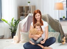Happy mother with adorable girl and teddy bear. Childhood, parenting and relationship concept - happy mother with adorable little girl and teddy bear over kids Stock Photo