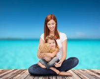 Happy mother with adorable girl and teddy bear Stock Photography