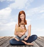 Happy mother with adorable girl and teddy bear Royalty Free Stock Images