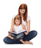 Happy mother with adorable little girl and book. Childhood, parenting and relationship concept - happy mother with adorable little girl reading book Stock Photography