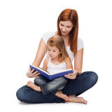 Happy mother with adorable little girl and book. Childhood, parenting and relationship concept - happy mother with adorable little girl reading book Royalty Free Stock Photos