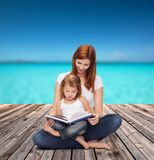 Happy mother with adorable little girl and book. Childhood, parenting and relationship concept - happy mother with adorable little girl reading book Royalty Free Stock Images