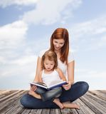 Happy mother with adorable little girl and book. Childhood, parenting and relationship concept - happy mother with adorable little girl reading book Royalty Free Stock Photo