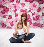 Happy mother with adorable little girl and book. Childhood, parenting and relationship concept - happy mother with adorable little girl reading book Stock Photo
