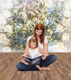 Happy mother with adorable little girl and book. Childhood, parenting and relationship concept - happy mother with adorable little girl reading book Royalty Free Stock Photography