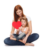 Happy mother with adorable little girl and heart. Childhood, parenting and relationship concept - happy mother with adorable little girl and red heart Stock Photo