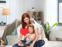 Happy mother with adorable little girl and heart. Childhood, parenting and relationship concept - happy mother with adorable little girl and red heart over kids Royalty Free Stock Photos